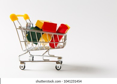 Close up of supermarket grocery push cart for shopping with yellow handle filled with multi-colored geometric shapes isolated on white background. Concept of shopping. Copy space for advertisement.