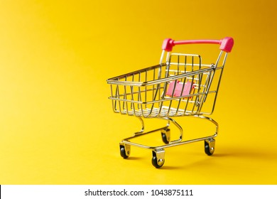 Close up of supermarket grocery push cart for shopping with black wheels and red plastic elements on handle isolated on yellow background. Concept of shopping. Copy space for advertisement.