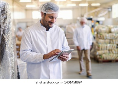 Close up of supervisor in uniform using tablet for checking data while standing in food factory.