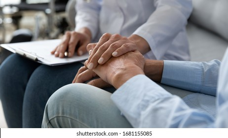 Close up of supportive female caregiver hold hand of mature grandmother visit patient at home, caring woman doctor support old senior grandma give consultation or help, elderly healthcare concept