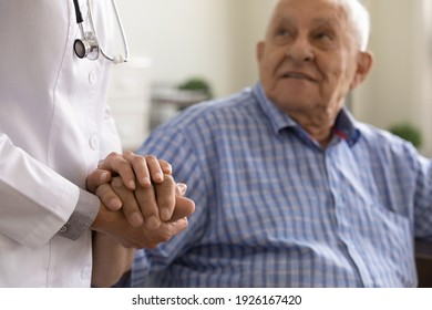 Close up supportive female caregiver wearing white uniform holding mature man hand, giving psychological help, expressing empathy and care, doctor comforting sick senior patient grandfather