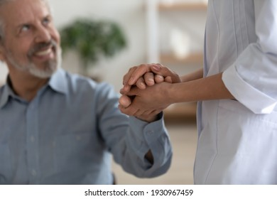 Close up of supportive female doctor in white medical uniform comfort caress hold senior male patient hand. Caring woman nurse or caregiver support optimistic mature man. Elderly healthcare concept.