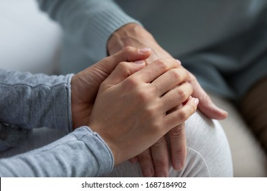 Close up of supportive grown-up daughter hug elderly mom hand talk share close intimate moment together, loving adult girl child comfort mature mother show care and support, family unity concept
