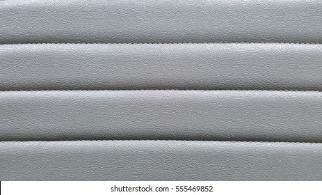 close up surface of grey leather seat, stitching, back ground