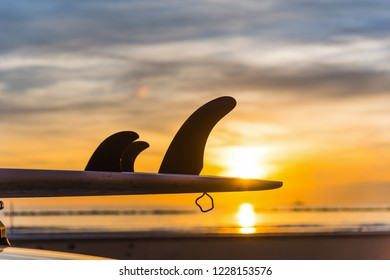 Close up of surfboard's fins at sunset