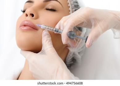 Close up of surgeon arms making  injection into female face. Serene young woman is lying and relaxing