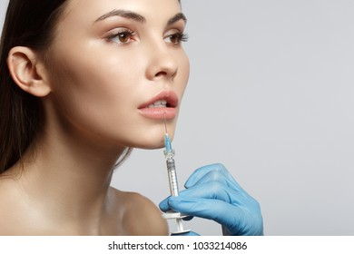 Close up of surgeon hand in glove injecting female lips by silicon liquid. Calm woman is looking forward with serenity. Isolated and copy space