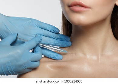 Close up of surgeon hands in glove injecting rejuvenating liquid into female neck. Beauty concept
