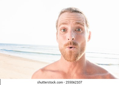 close up of surprised handsome man at the beach, looking at the camera.
