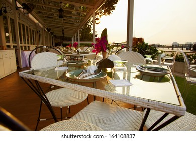 Close up surved table with tableware for dinner in the modern street cafe against sunset