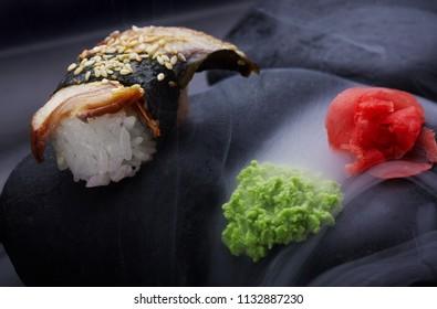 Close up of sushi nigiri with eel .Sushi. On dark stone with fog .Creative shot. Japanese athmophere.Copy space.Minimalism