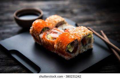 close up of sushi rolls on black tray