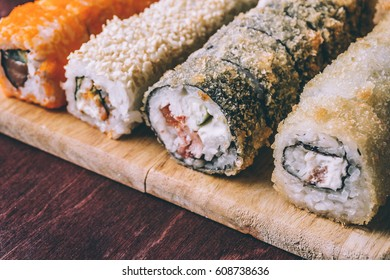 Close up of sushi rolls set served on wooden dish, copy space, toned photo