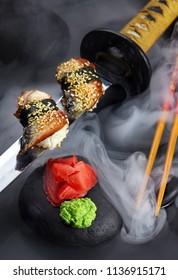 Close up of sushi set with chopsticks .Sashimi.Nigiri. On katana sword with fog .Wasabi and ginger on black stone.Creative shot. Japanese athmophere.
