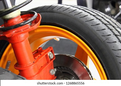Close up suspension shock adsorber strut with spring,brake disc and alloy wheel of sport car