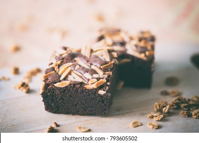 Close up sweet chocolate brownie with almond topping, vintage color
