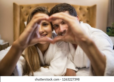 Close up of  sweet couple making heart with hands. Adorable woman and handsome man in love looking at camera and smiling on background. Concept of relationships, love and honeymoon in hotel.