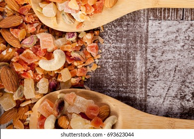 Close up of sweet dried fruits and roasted nuts in wooden spoon on wooden background in studio photo