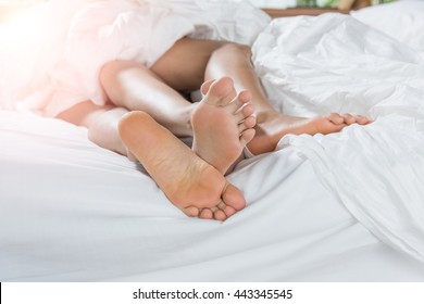 Close up Sweet Partners Soles on White Bed. (intentional sun glare)