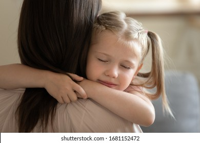 Close up of sweet small preschooler girl embrace young mother showing love and care enjoy tenderness at home, cute little daughter and mom hug cuddle share intimate tender moment together