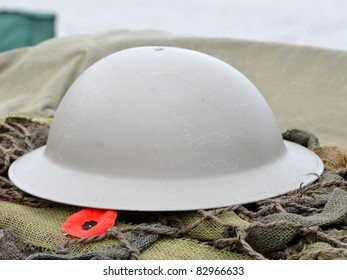 close up of a symbol of remembrance the Remembrance poppy lying beside a military helmet