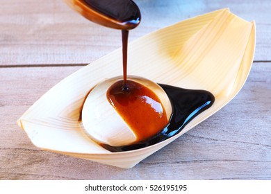 Close up of syrup on a japanese water drop cake on a wooden table.