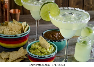 Close up of table filled with glasses filled with classic lime margarita cocktails with tortilla chips, salsa and fresh guacamole