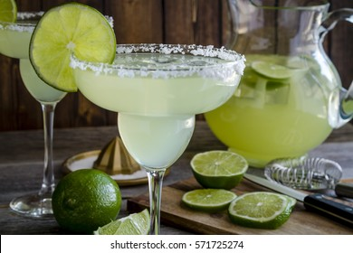 Close up of table filled with glasses and pitcher filled with classic lime margarita cocktails, fresh limes and barware