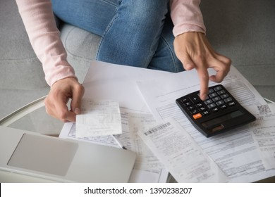 Close up table full with utility bills, cash vouchers and woman hands use calculator summarizes cost money manages finances family budget, accountant doing paperwork job at home, bookkeeping concept