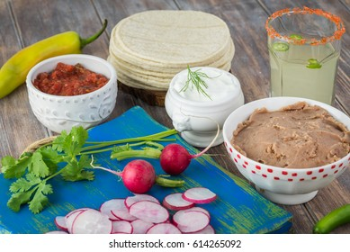 Close up of table with ingredients for vegetarian corn tacos -   refried beans, corn tortilla, radish, green onion.