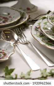 Close up of a table set up with colorful porcelain dining set and silverware for a special occasion meal.  Gold painting on the edges.