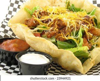 close up of taco salad with beef in a taco shell bowl with salsa and sour cream on side