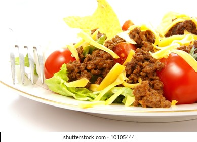 Close up of Taco salad with seasoned ground beef, lettuce, tomato, cheese, sour cream, salsa, and corn chips