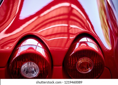 Close up of tail light detail of modern luxury sportscar with reflection on red paint after wash & wax. Rear view of supercar break lights. Concept of car detailing and paint protection background.