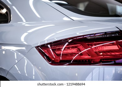 Close up of taillight detail of modern luxury sportscar with reflection on white paint after wash & wax. Rear view of supercar break lights. Concept of car detailing and paint protection background.