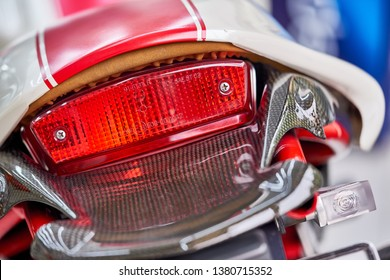 Close up of taillight detail of modern luxury sports bike with reflection on paint after wash & wax. Rear view of shiny superbike. Concept of car detailing and paint protection. Automotive background.