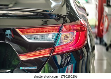 Close up of taillight detail of modern luxury car with reflection on black paint after wash & wax. Rear view of sedan. Concept of car detailing and paint protection background.
