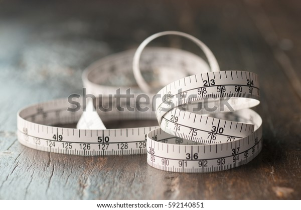 Close up tailor measuring tape on wooden table background. White measuring tape shallow depth of field.