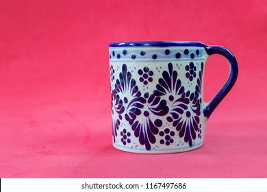 A close up of a Talavera cup with a red background in a very serious and sexy attitude