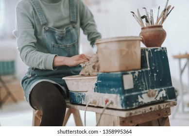 Close up of talented craftswoman in denim overalls sitting on wooden bench and preparing raw clay for pottery