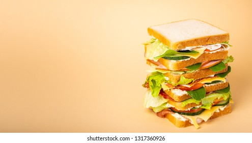 Close up of tall whole tasty sandwich with cheese, ham, prosciutto, fresh lettuce, tomatoes, cucumbers on pastel yellow background. Healthy gourmet sandwich for breakfast or lunch. Space for text