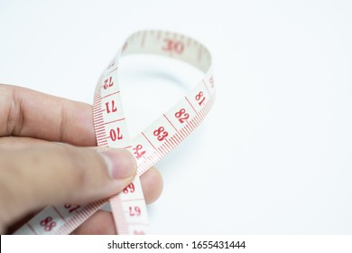 Close up Tape measure in hand on white background.