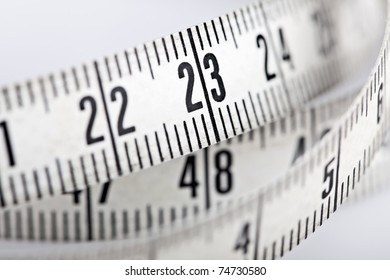 close up of a tape measure rolled on white background
