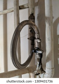 Close up of taps and flexible filling loop hose for pressure adjustment on a combi boiler central heating system