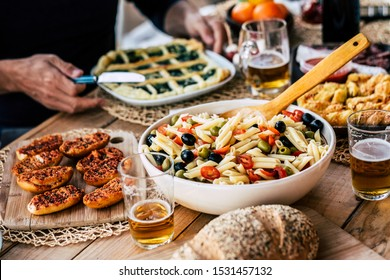 Close up of tasty and colorful rustic table full of food -italian pasta salads. and gourme ishes beer on glasses - people enjoying and celebrating friendship together at home or restaurant