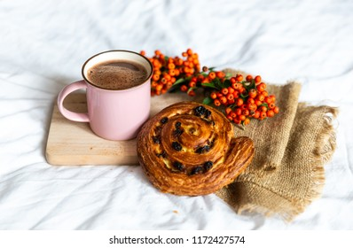 Close up of tasty and delicious breakfast in bed with cake and cacao. Fresh bake and coffee in pink cup on wooden board, near orange autumn berries. Concept of autumn morning.