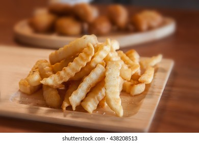 Close up of Tasty french fries on cutting board, on wooden table background