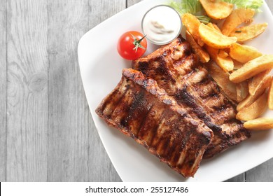 Close up Tasty Grilled Pork Rib and Fried Potatoes on White Plate with White Sauce on a Plate. Placed on Wooden Table With Copy Space.