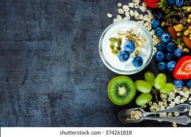 Close up of tasty ingredients (oat flakes, kiwi, berries with yogurt and seeds) for breakfast or smoothie on dark vintage background - Healthy food, Diet, Detox, Clean Eating or Vegetarian concept.