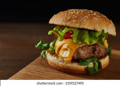 close up of tasty meat burger with cheese and greenery on wooden chopping board